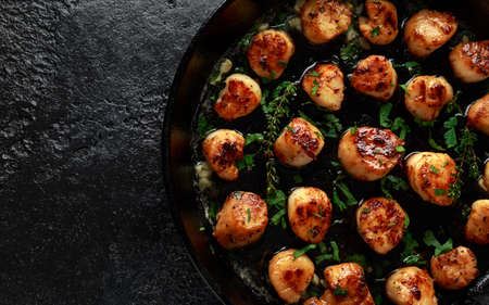 Scallops seared in garlic and parsley butter served in cast iron skillet Stock fotó