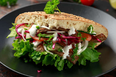 Doner kebab, fried lamb meat with vegetables and garlic sauce in turkish bread Archivio Fotografico - 119398028