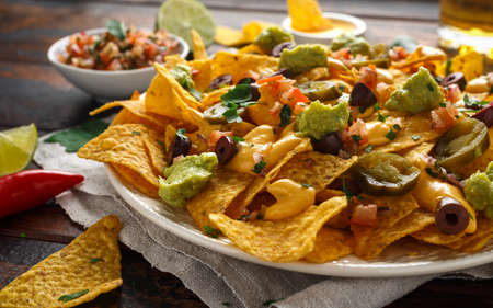 Mexican nachos tortilla chips with olives, jalapeno, guacamole, tomatoes salsa, cheese dipand beer. Imagens