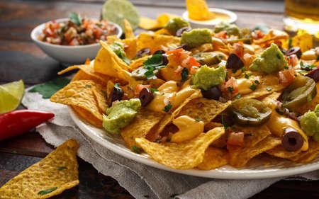 Tortilla chips de nachos mexicanos con aceitunas, jalapeño, guacamole, salsa de tomate, salsa de queso y cerveza.