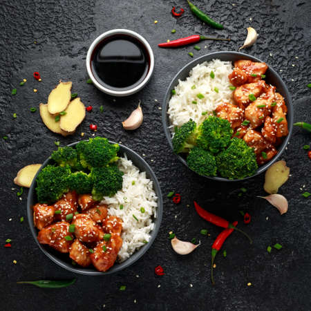 Teriyaki chicken, steamed broccoli and basmati rice served in two Asian clay bowls Foto de archivo - 119783728