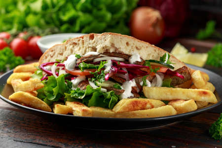 Doner kebab, fried lamb meat with vegetables, fries and garlic sauce in turkish bread Archivio Fotografico - 119783856