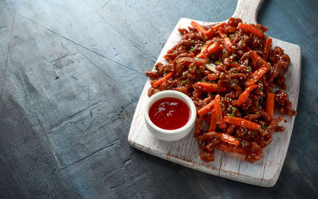 Crispy shredded beef with carrots and sweet chilli sauce on white wooden board. Chinese takeaway food