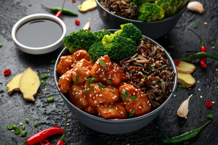 Teriyaki chicken, steamed broccoli and wild rice served in two Asian clay bowls Foto de archivo - 119783985