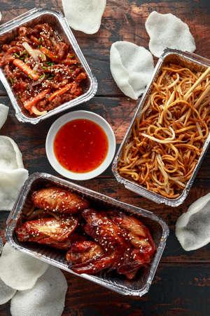 Plats à emporter chinois. Bœuf effiloché croustillant, ailes de poulet aigre-douce, nouilles aux œufs avec fèves germées, ananas, trempette au piment et craquelins aux crevettes