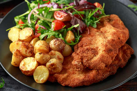 Homemade breaded pork schnitzel with roast potato and vegetables
