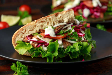 Doner kebab, fried lamb meat with vegetables and garlic sauce in turkish bread Archivio Fotografico - 120217561