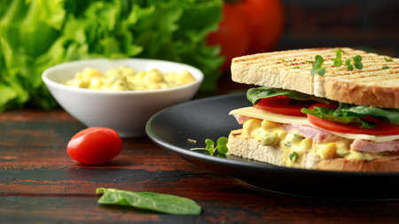 Sandwich with ham, cheese, tomatoes, spinach, corn, mayonnaise, mustard, gherkins, toasted bread and potato chips.