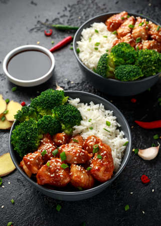 Teriyaki chicken, steamed broccoli and basmati rice served in two Asian clay bowls Foto de archivo - 120217778