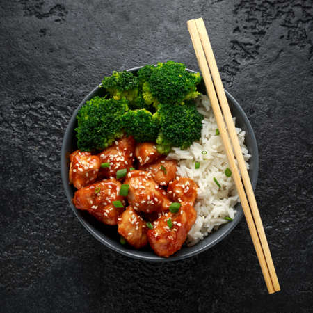 Teriyaki chicken, steamed broccoli and basmati rice served in bowl with chopsticks Foto de archivo - 120217779