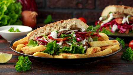 Doner kebab, fried lamb meat with vegetables, fries and garlic sauce in turkish bread. Archivio Fotografico - 120217935