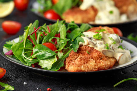 Chicken steak in Breadcrumbs with mushrooms and vegetables Stock Photo