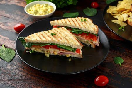 Sándwich de jamón, queso, tomate, espinaca, maíz, mayonesa, mostaza, pepinillos, pan tostado y papas fritas.