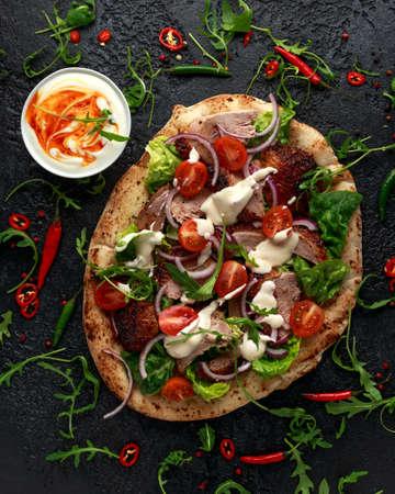 Roasted Duck kebab on flat bread with yogurt dip and salad Фото со стока