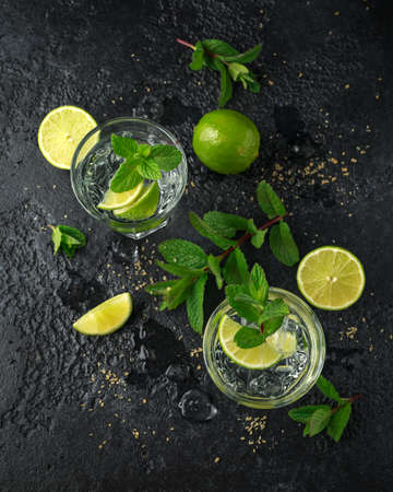 Mojito cocktail with Rum, lime and mint in glass. Summer cold drink with ice.