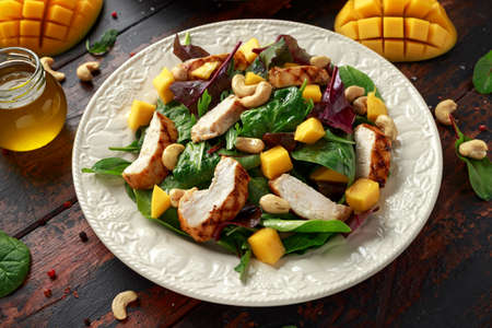 Grilled Chicken Mango salad with nuts and vegetables. Healthy food Stock Photo