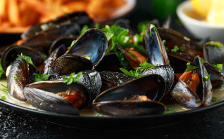 Mussels with white wine, garlic, lemon and herbs in a plate, French fries. rustick background. Seafood