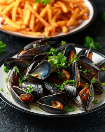 Mussels with white wine, garlic, lemon and herbs in a plate, French fries. rustick background. Seafood.