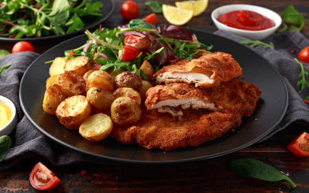 Homemade breaded pork schnitzel with roast potato and vegetables.