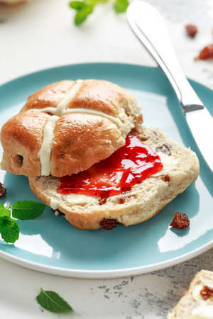 Hot cross buns in blue plate served with butter, strawberry jam and cup of tea Stock Photo