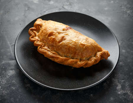 Traditional Cornish pasty filled with beef meat, potato and vegetables on black plate. Imagens