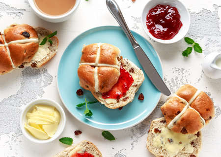 Hot cross buns in blue plate served with butter, strawberry jam and cup of tea. Stock Photo