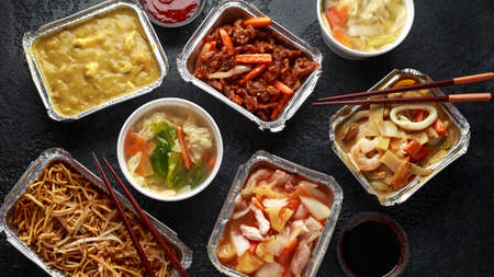 Chinese takeaway food. Pork Wonton dumpling soup, Crispy shredded beef, sweet and sour pineapple chicken, egg noodles with bean sprouts, curry. Stock Photo