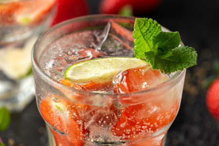 Strawberry Mojito cocktail with Rum, lime and mint in glass. Summer cold drink with ice Stock Photo