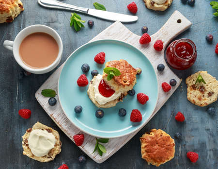 Classic scones with clotted cream, strawberries jam, english Tea and other fruit. Imagens
