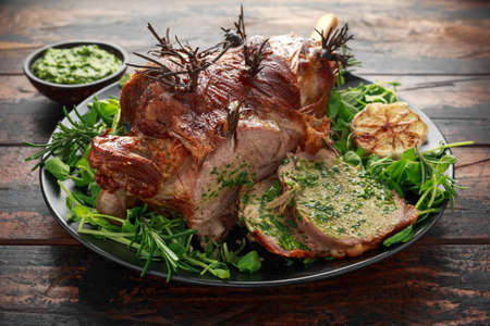 Roast Lamb leg with mint sauce, rosemary and garlic on black plate, wooden table.