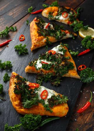 Homemade Kale and red chilli flatbread pizza with mozzarella Фото со стока