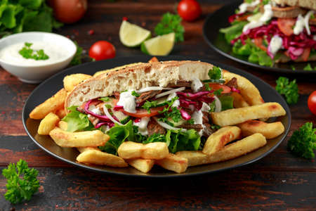 Doner kebab, fried lamb meat with vegetables, fries and garlic sauce in turkish bread Archivio Fotografico - 122798332