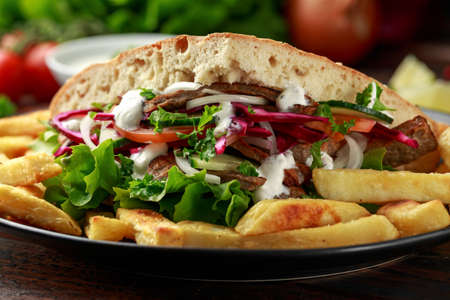 Doner kebab, fried lamb meat with vegetables, fries and garlic sauce in turkish bread Archivio Fotografico - 122798333