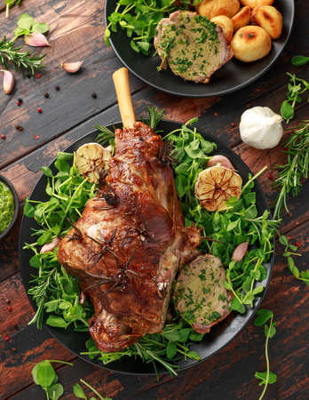 Roast Lamb leg with mint sauce, rosemary and garlic. on black plate, wooden table. Stock fotó