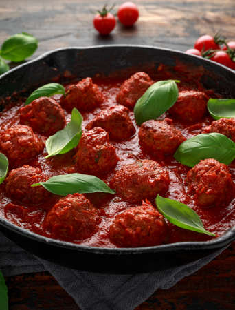 Homemade Meatballs in iron cast with sweet and hot tomato sauce, basil. On wooden table. Imagens