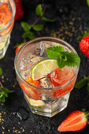Strawberry Mojito cocktail with Rum, lime and mint in glass. Summer cold drink with ice. Stock Photo