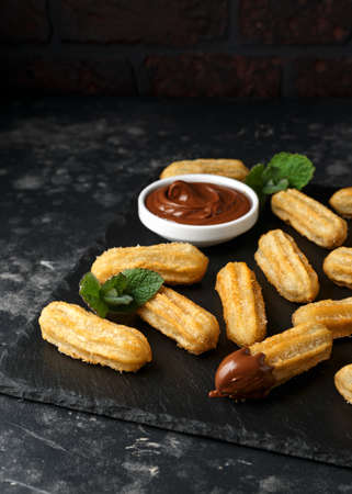 Churros with chocolate dipping sauce. sugar and cinnamon.