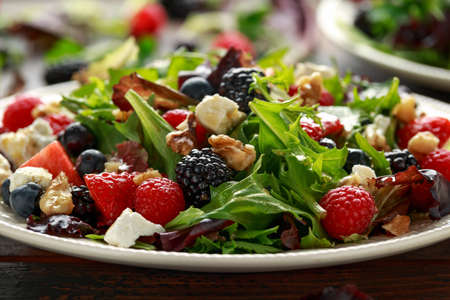 Fresh Fruit Salad with blueberry, strawberry raspberry, walnuts, feta cheese and green vegetables. healthy summer food