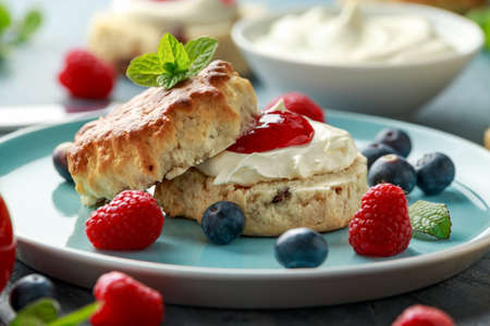 Classic English scones with clotted cream, strawberries jam and other fruit Stock Photo - 123050497