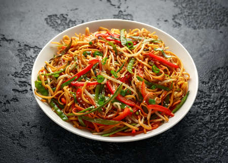 Chow mein, noodles and vegetables dish with wooden chopsticks Standard-Bild
