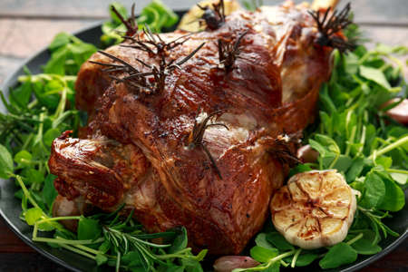 Roast Lamb leg with rosemary and garlic. on black plate, wooden table