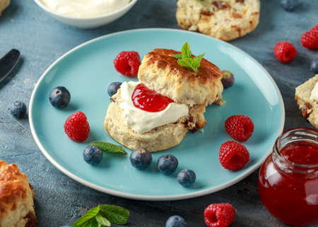 Classic English scones with clotted cream, strawberries jam and other fruit