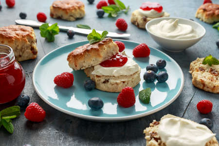 Classic English scones with clotted cream, strawberries jam and other fruit.