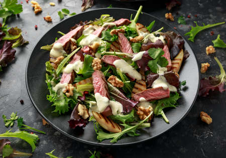 Grilled Beef Steak salad with pears, walnuts and greens vegetables and blue cheese sauce. healthy food