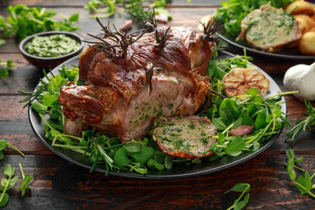 Roast Lamb leg with mint sauce, rosemary and garlic. on black plate, wooden table. Stock Photo