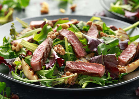 Grilled Beef Steak salad with pears, walnuts and greens vegetables and blue cheese sauce. healthy food.