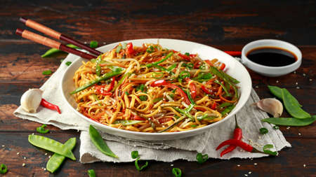Chow mein, noodles and vegetables dish with wooden chopsticks Stock fotó