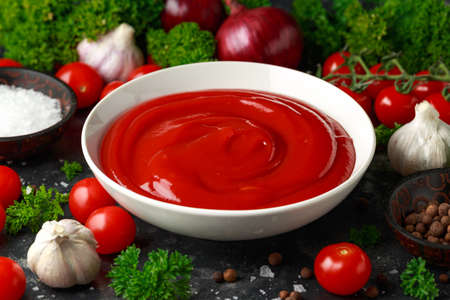 Homemade ketchup sauce in white bowl with vegetables and herbs Stock Photo