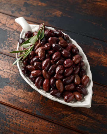 Pitted kalamata olives in bowl on rustic wooden background