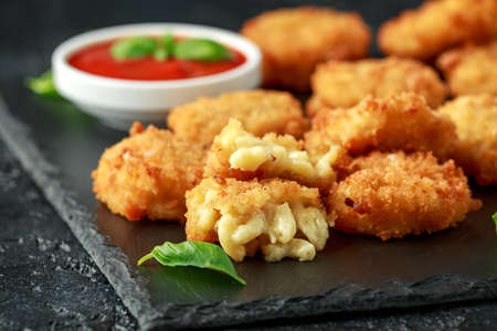 Fried Mac, macaroni and Cheese Bites in breadcrumbs with ketchup sauce